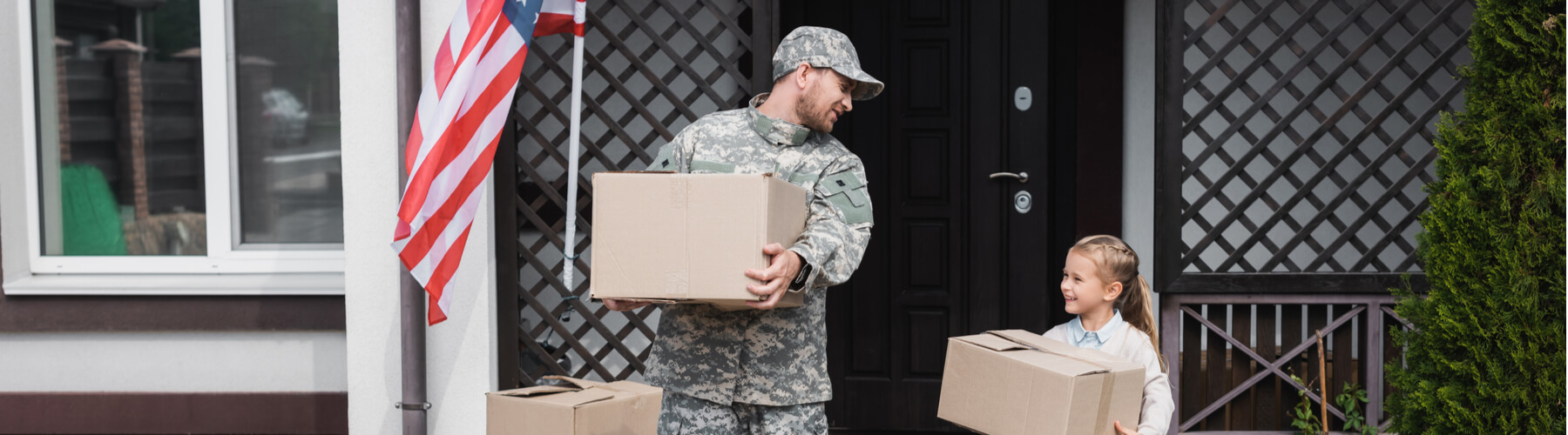 Father in military uniform and daughter holding cardboard boxes near house with american flag, moving in or out of military house