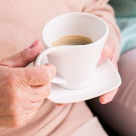 Nursing home patient, holding coffee